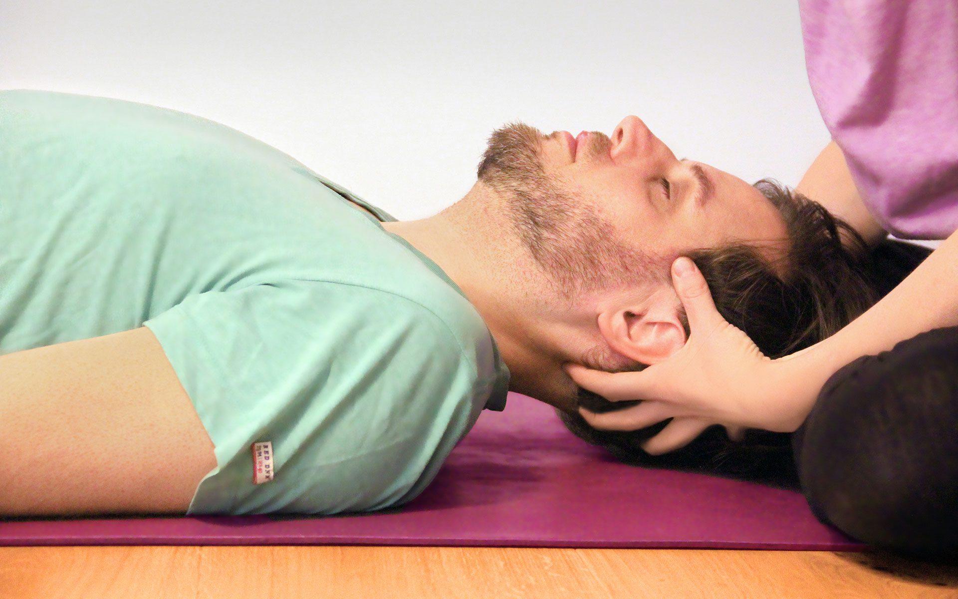 Einem liegenden Mann massiert Ulrike Pape den Kopf